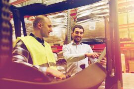 happy-men-with-tablet-pc-and-forklift-at-warehouse-PR2CLBG (1)